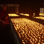 Ani Rinchen lighting some of the 10,000 butterlamps dedicated to Uncle Sherab Palden